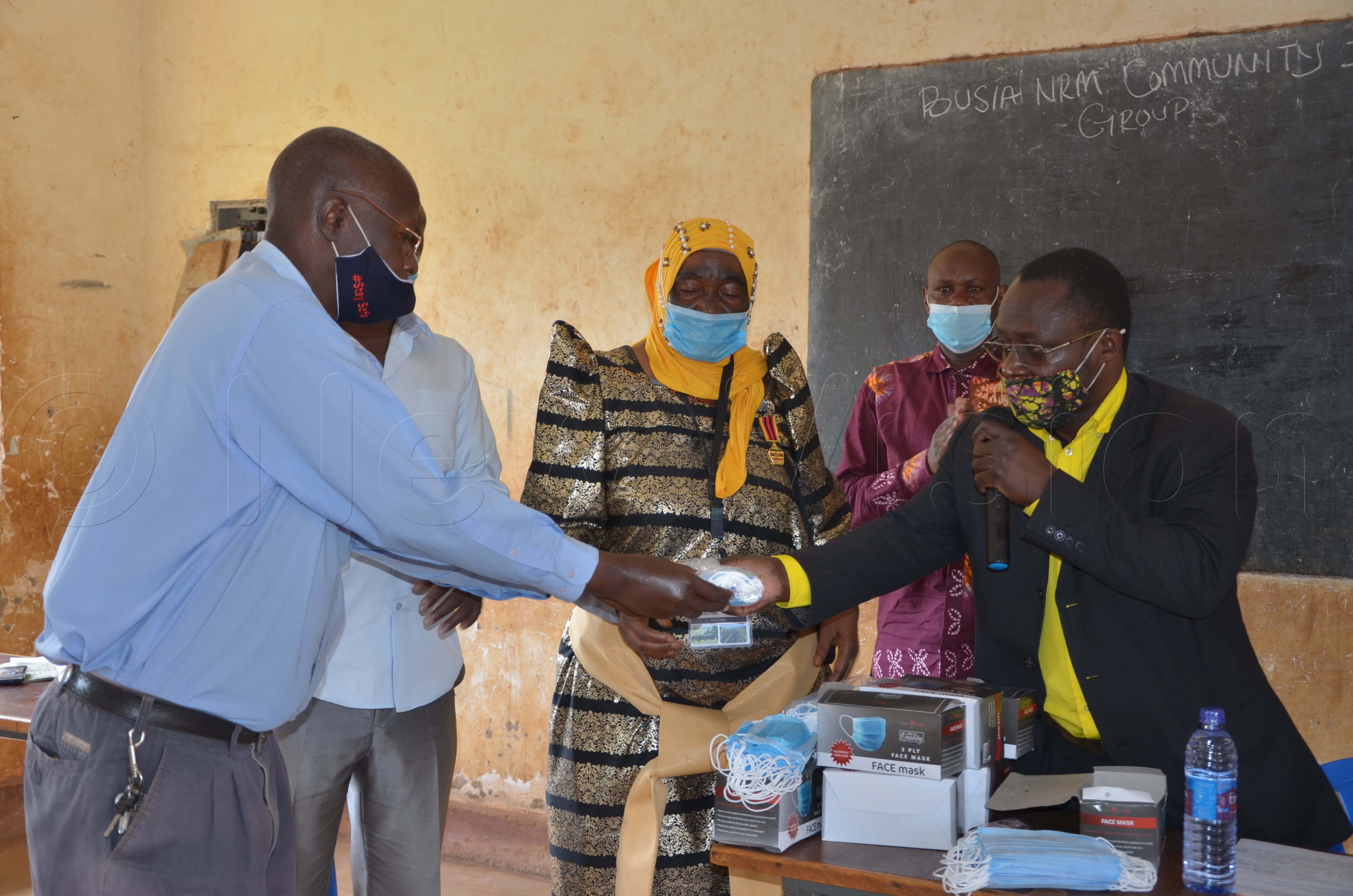 Stephen Mugeni Wasike LC5 Busia(right) handing over face masks to George Barasa LC1 Nangwe shops village