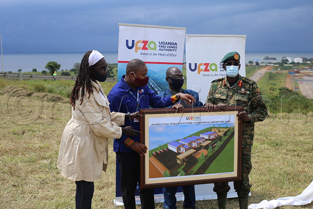 Former board chairman Eng. Dr. Frederick Kiwanuka (second right), former member Grace Achire Labong (left) and UFZA executive director Hez Alinda (second left) hand over architectual designs of the first public free zone to Lt. Gen. James Mugira (right), the managing director of the National Enterprises Corporation for development at Entebbe Airport in September 2020. (Photo by Benon Ojiambo)