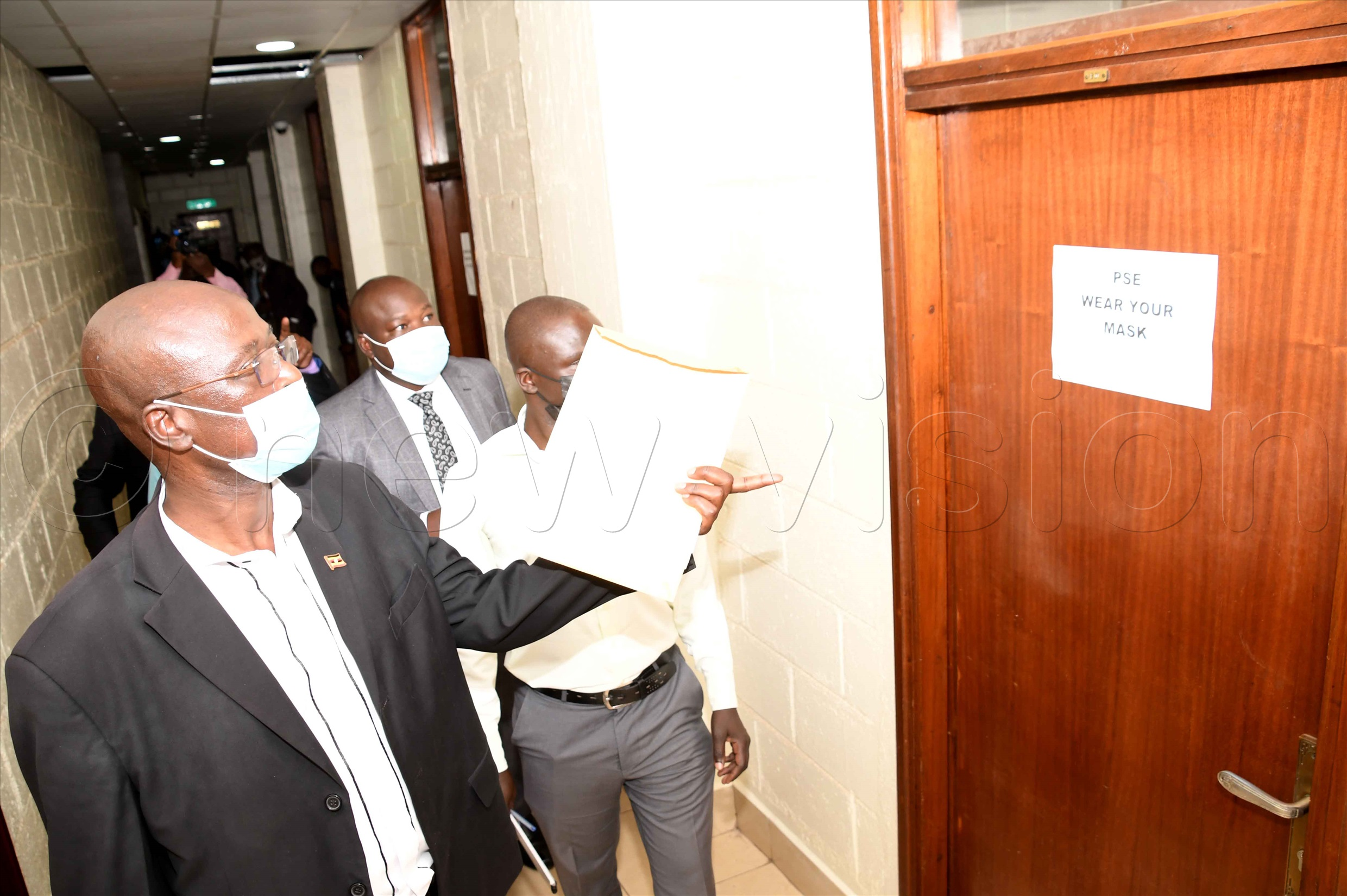 Gulu City officials walking through the Parliament corridors to the CID integration room. Photo by Maria Wamala
