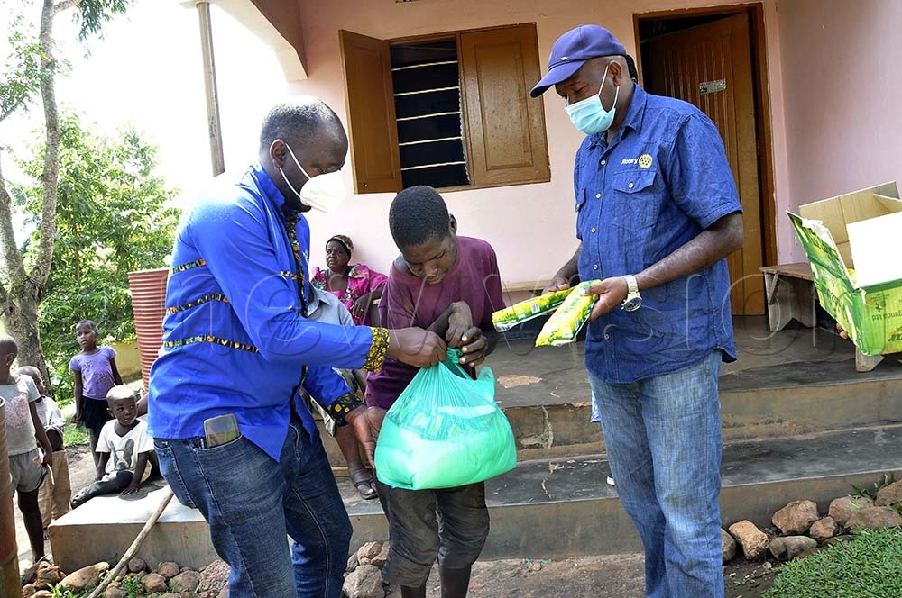 Shafiq Lule, 26, (M) a person with special needs receiving food relief from Philip Ddungu Yeko (L) Project director Buloba Rotary Club and Nasuru Ziraba (R) member Rotary Club Buloba during the distribution of food relief to needy resident of Bujuuko. (All Photos by Ramadhan Abbey)