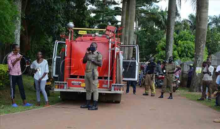 Owa Poliisi Ng'akuba Essimu. Emabega Ye Mmotoka Ezikiza Omuliro.