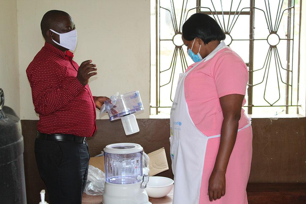Kansiime Stella Enroled Nurse at Nyakitokole HCII, Karangura SC in Kabarole (L) receives safe drinking water station from IRC WASH Advisor.