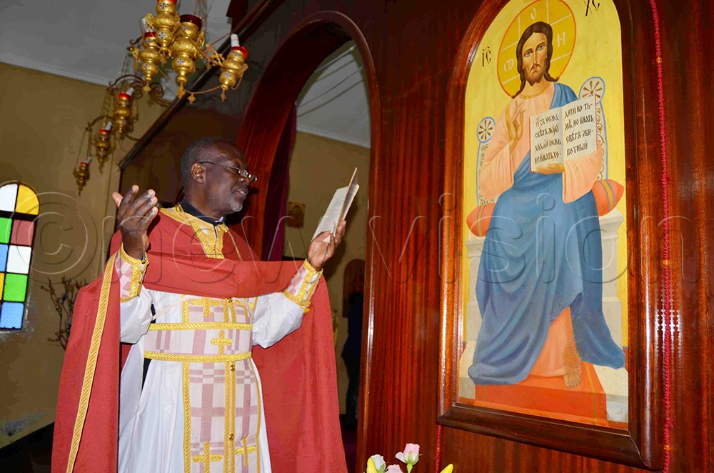 An Orthodox priest, Fr Isabirye reciting a prayer during Metropolitan Lwanga