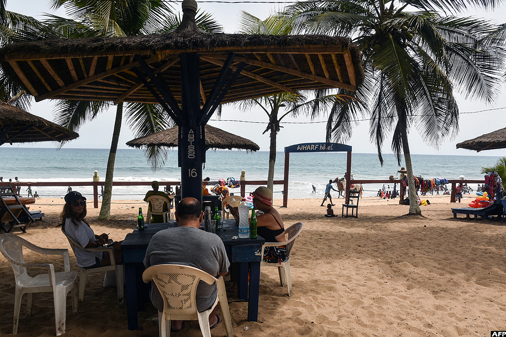 A general view of people sitting at a table on a beach in front of a hotel in Grand-Bassam